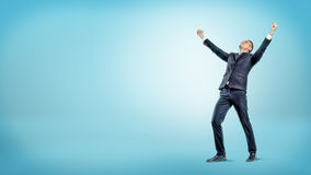 Un uomo d'affari allegro che sta con le mani si è alzato nella vittoria e nel cercare sul fondo blu fotografia stock