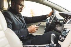 Un uomo d'affari che conduce un'automobile costosa tiene un telefono cellulare in sua mano Vita affrettata fotografie stock