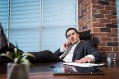 Un uomo d'affari che parla su un telefono cellulare, uomo d'affari che parla sulla t Immagini Stock Libere da Diritti