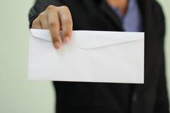 Un uomo d'affari che passa in una busta in bianco Fotografia Stock Libera da Diritti