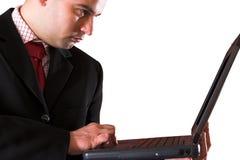 Un uomo d'affari che per mezzo del computer portatile Immagini Stock Libere da Diritti