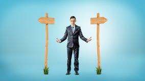 Un uomo d'affari che sta fra due segni di legno che indicano le direzioni differenti fotografia stock