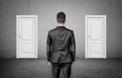 Un uomo d'affari con la sua parte posteriore girata sta fra due porte bianche chiuse identiche Immagini Stock