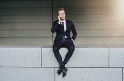 Un uomo d'affari con le gambe attraversate parla il telefono immagine stock