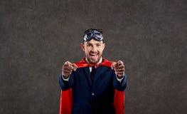 Un uomo d'affari in un costume del supereroe è un vincitore immagine stock libera da diritti