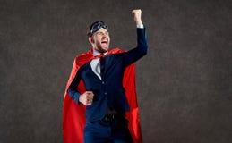 Un uomo d'affari in un costume del supereroe è un vincitore immagini stock