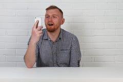 Un uomo d'affari dei pantaloni a vita bassa sta parlando sul telefono È molto emozionale Su una priorità bassa bianca Isolato Uom immagini stock libere da diritti