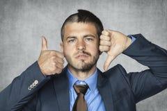 Un uomo d'affari di due facial non può decidere immagine stock