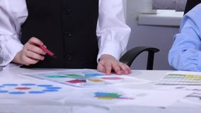 Un uomo d'affari di due ragazzini che esamina computer portatile ed indicato sui grafici stock footage