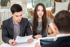 Un uomo d'affari di tre giovani che si siede alla tavola e che discute busi Fotografia Stock Libera da Diritti