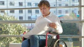 Un uomo d'affari disabile su una sedia a rotelle in una finestra con attingere un grande foglio di carta, discute il lavoro dal t archivi video