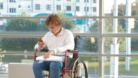 Un uomo d'affari disabile su una sedia a rotelle in una finestra con attingere un grande foglio di carta, discute il lavoro dal t stock footage