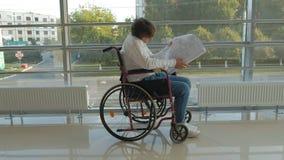 Un uomo d'affari disabile su una sedia a rotelle in una finestra con attingere un grande foglio di carta, discute il lavoro dal t video d archivio