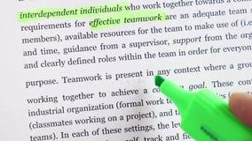 Un uomo d'affari evidenzia la definizione del lavoro di squadra di parola con un indicatore nel testo stock footage