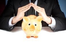 Un uomo d'affari fa con la sua mano una casa dietro un porcellino salvadanaio, concetto per l'affare e risparmia i soldi Immagini Stock Libere da Diritti