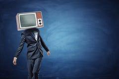 Un uomo d'affari instabile che sta irregolarmente con una grande retro TV sulla sua testa che mostra rumore grigio Fotografia Stock Libera da Diritti