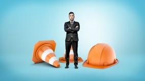 Un uomo d'affari minuscolo con le mani attraversate che stanno accanto ai coni a strisce giganti di traffico e ad un casco aranci Fotografia Stock Libera da Diritti
