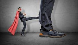 Un uomo d'affari minuscolo in un capo rosso e in un eyemask che danno dei calci una ritirata al piede gigante Fotografia Stock Libera da Diritti