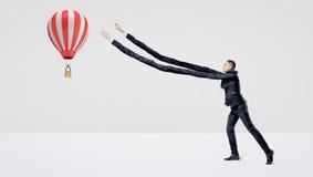 Un uomo d'affari nella vista laterale che prova a prendere una grande mongolfiera di volo con le sue armi extra-lunghe Fotografie Stock