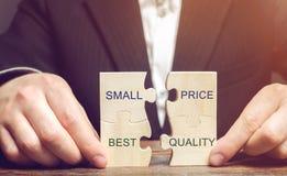 Un uomo d'affari raccoglie i puzzle di legno con il piccolo prezzo di parole - migliore qualità Il concetto degli affari proficui immagine stock