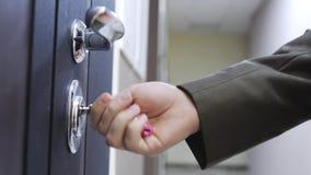 Un uomo d'affari sblocca la porta di una casa con la chiave ed entra 3840x2160 archivi video