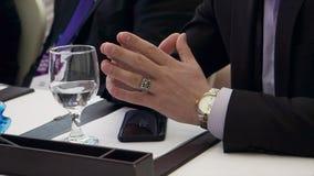 Un uomo d'affari si siede ad uno scrittorio che le sue mani aspettano per iniziare una riunione azione L'uomo d'affari alla riuni immagine stock
