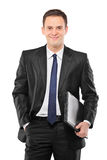 Un uomo d'affari sorridente che tiene un computer portatile Fotografia Stock Libera da Diritti