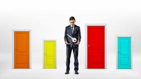 Un uomo d'affari sta accanto a molte piccole porte multicolori ed esamina una grande chiave che appende sopra le sue mani fotografia stock