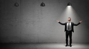 Un uomo d'affari sta su fondo concreto nell'ambito della luce di singola lampada industriale funzionante Fotografie Stock