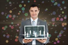 Un uomo d'affari sta tenendo un computer portatile contro il fondo dei grafici dell'interfaccia Fotografie Stock Libere da Diritti