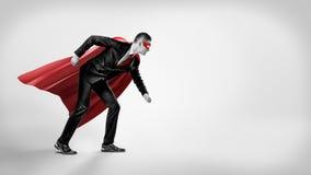 Un uomo d'affari in un capo rosso del supereroe ed in una maschera che stanno nella posizione di linea di partenza su fondo grigi Fotografie Stock Libere da Diritti