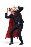 Un uomo d'affari in un capo rosso dell'eroe e una maschera nella vista frontale che si accovacciano nel timore su fondo bianco Fotografia Stock
