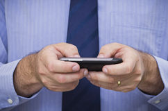 L'uomo d'affari scrive il messaggio dello smartphone dello schermo attivabile al tatto Fotografia Stock