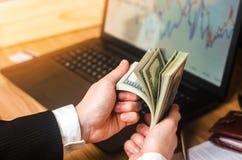 Un uomo d'affari in un vestito conta i dollari ad una tavola nelle mani di un computer portatile e dei grafici finanziari Un conc fotografia stock libera da diritti
