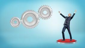 Un uomo d'affari vittorioso sta su un pulsante rosso gigante vicino a tre ingranaggi di collegamento immagine stock