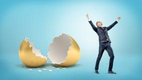 Un uomo d'affari vittorioso sta vicino ad un grande guscio d'uovo dorato rotto su fondo blu immagini stock