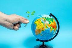 Un uomo d? un germoglio verde al globo, fondo blu immagini stock libere da diritti