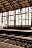 Un uomo da solo alla stazione ferroviaria vuota con la grande finestra macchiata b fotografia stock