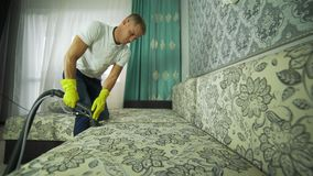 Un uomo da una società di pulizia si è impegnato nella pulizia del sofà Uomo in panno di pulizia uniforme del sofà con pulitore a archivi video