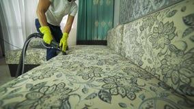 Un uomo da una società di pulizia si è impegnato nella pulizia del sofà Uomo in panno di pulizia uniforme del sofà con pulitore a video d archivio