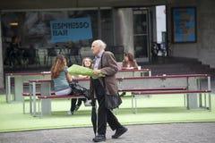Un uomo dai capelli grigi anziano in un vestito con un mazzo dei fiori cammina dopo un caffè della via Immagini Stock Libere da Diritti