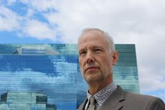Un uomo davanti ad un edificio per uffici blu Fotografia Stock