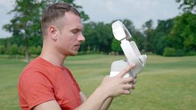 Un uomo decolla la sua cuffia avricolare di VR dalla sua testa nel parco