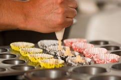 Un uomo del forno sta preparando i biscotti deliziosi di un natale in un deposito del forno, aggiungente la pasta dentro degli in Fotografia Stock Libera da Diritti