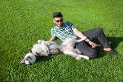 Un uomo del Medio-Oriente di modo con la barba e lo stile di capelli di modo sta riposando e gode di su bella erba verde Immagine Stock Libera da Diritti