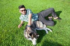 Un uomo del Medio-Oriente di modo con la barba e lo stile di capelli di modo sta riposando e gode di su bella erba verde Fotografia Stock Libera da Diritti