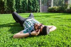 Un uomo del Medio-Oriente di modo con la barba, stile di capelli di modo sta riposando su bello tempo del giorno dell'erba verde Fotografia Stock Libera da Diritti