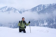 Un uomo del viaggiatore con zaino e sacco a pelo che va in montagne di inverno Fotografia Stock