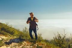 Un uomo del viaggiatore scala alla cima di una montagna contro un fondo delle nuvole un giorno soleggiato Stile di vita di viaggi Immagine Stock