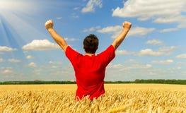 Un uomo dell'agricoltore in una maglietta rossa che sta in un campo di grano tira le sue mani verso il cielo Composizione concett fotografia stock